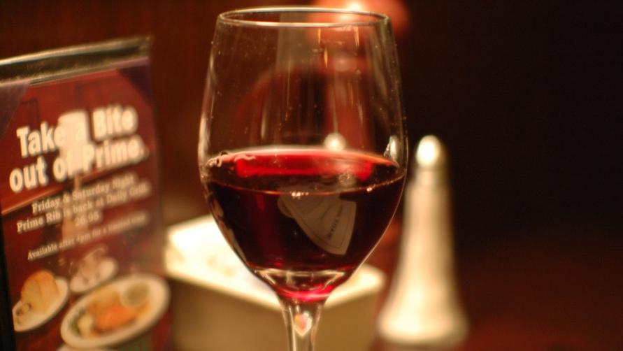 Бокал вина на столе.