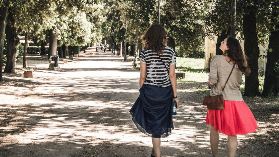 Девушки гуляют по аллее