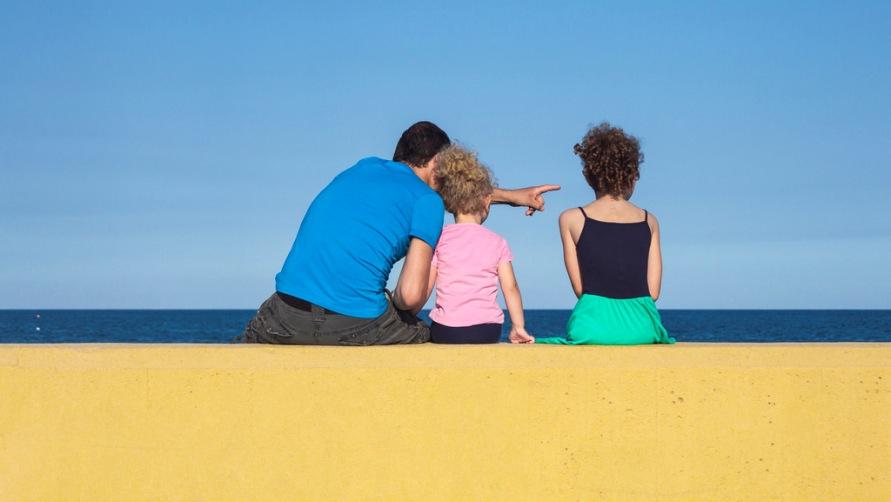 Отец с дочерьми на пляже.
