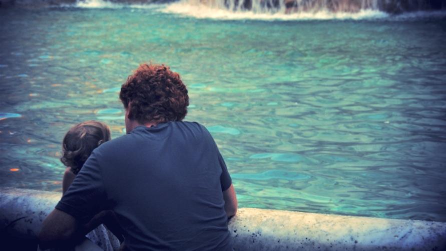 Отец с дочерью у фонтана