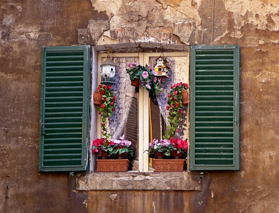 Красивое окошко с цветами на средневековой стене.