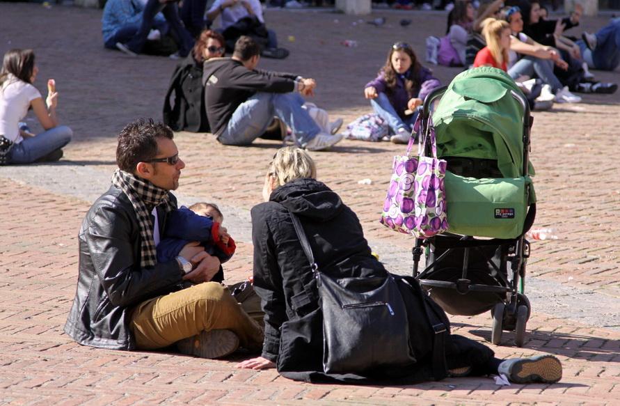 Папа, мама и малыш на отдыхают на площади.