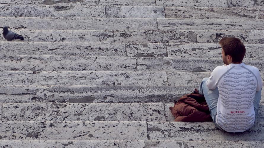 Мужчина сидит на ступенях.